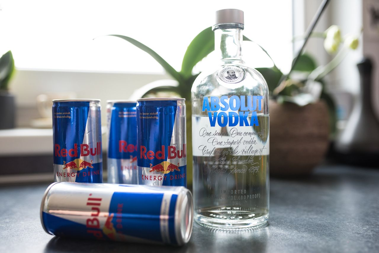 Absolut vodka bottle with cans of red bull