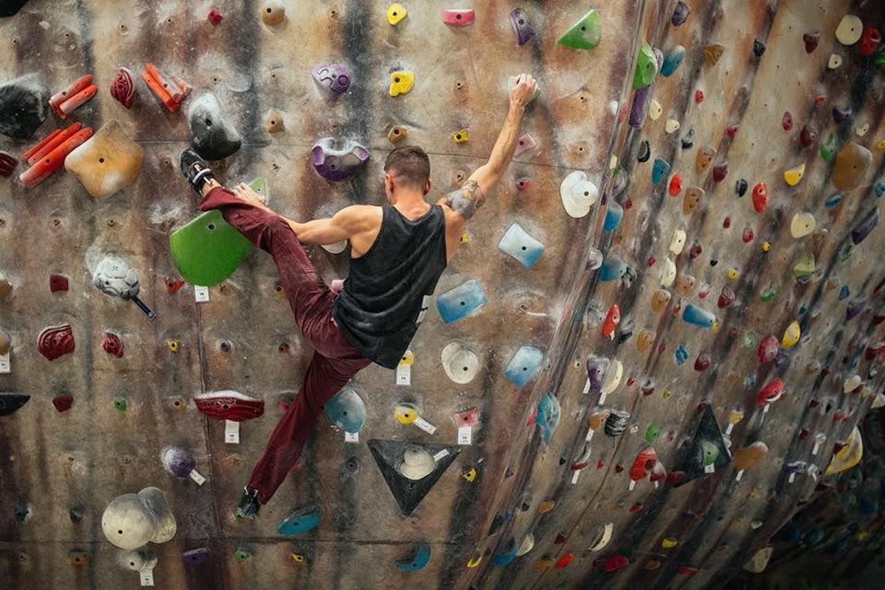 Man ascending rock wall in a rock climbing gym