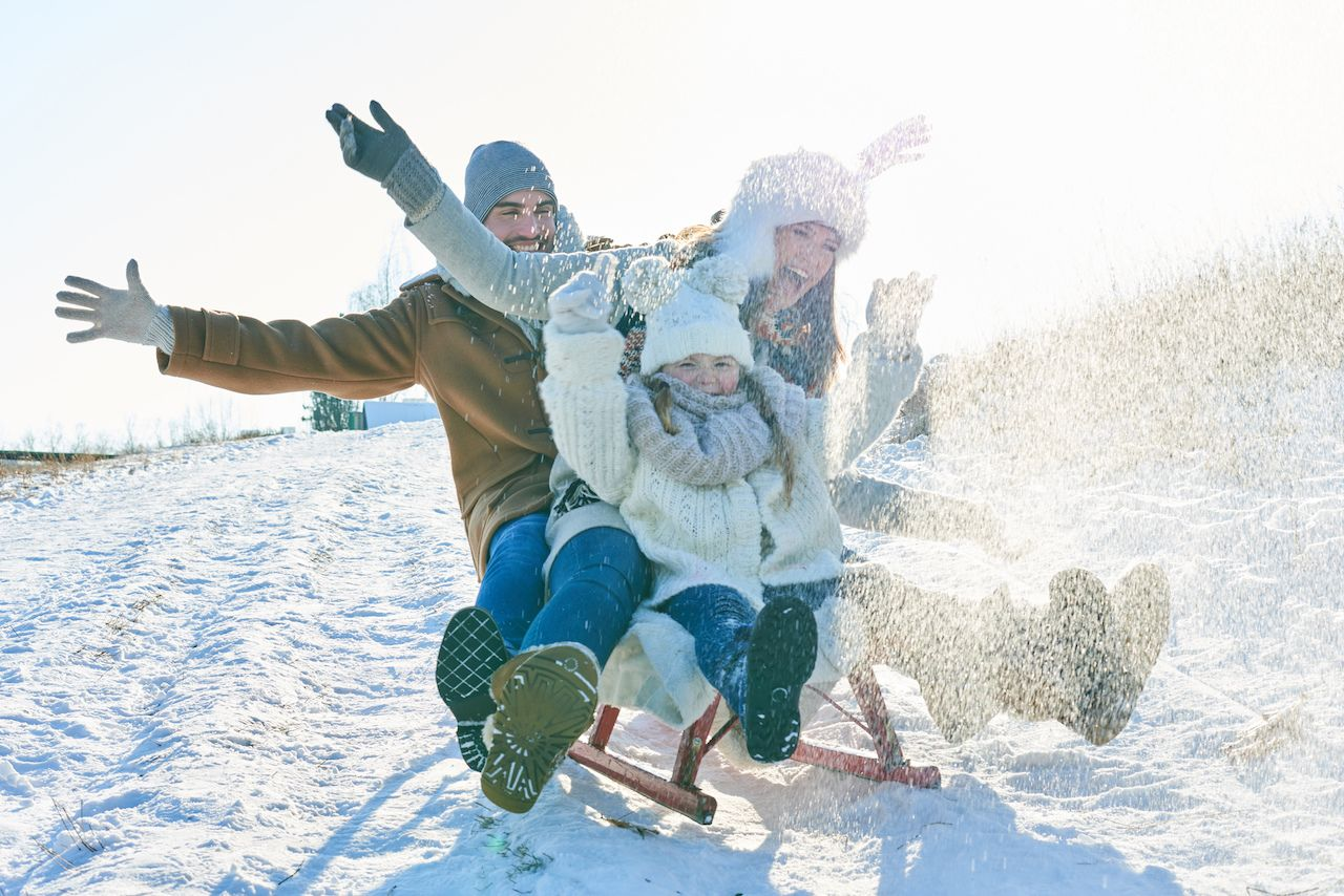 Family driving sled on the snow and having fun in winter