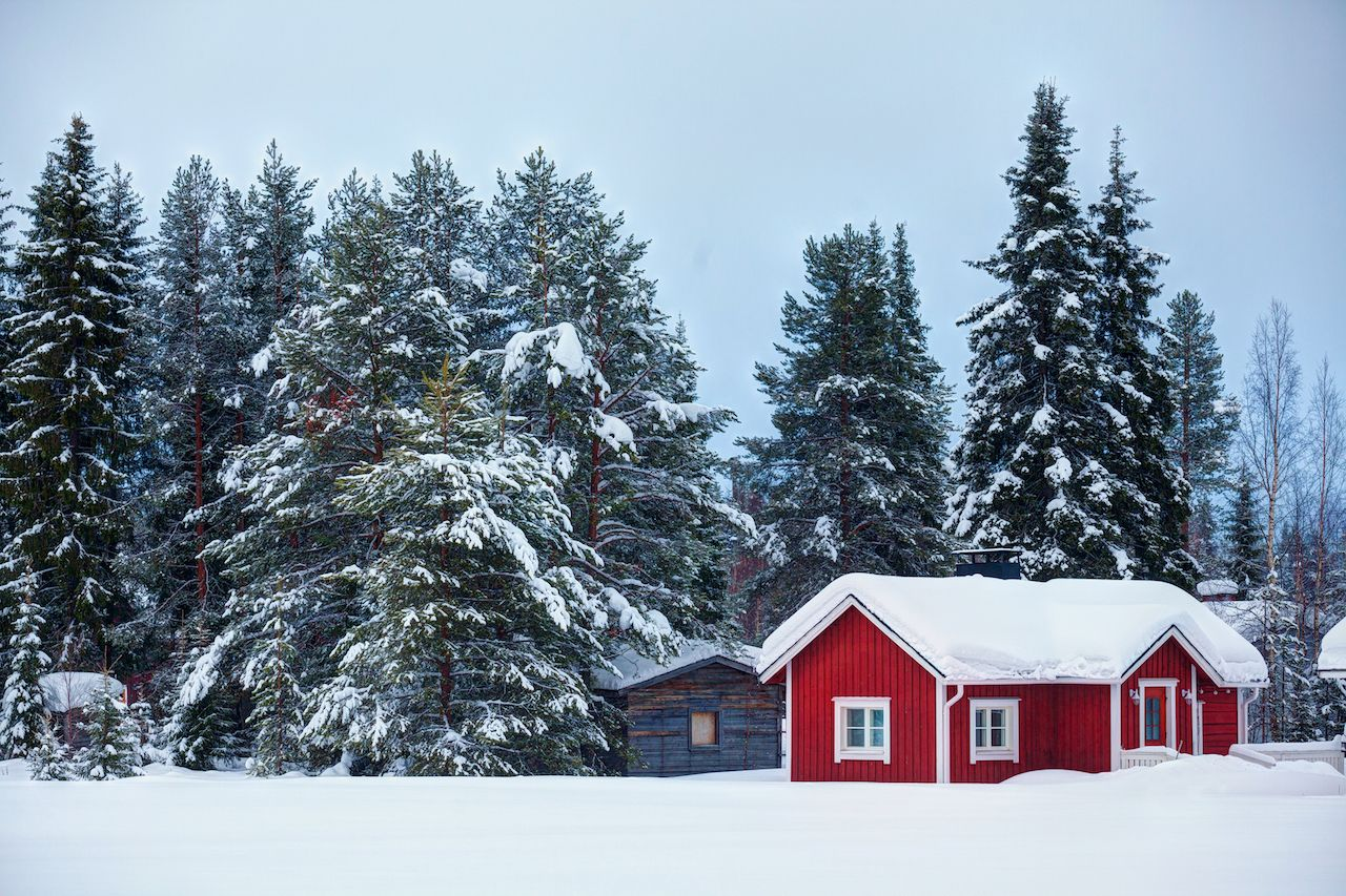 Finnish winter landscape with red wooden finnish house covered with snow