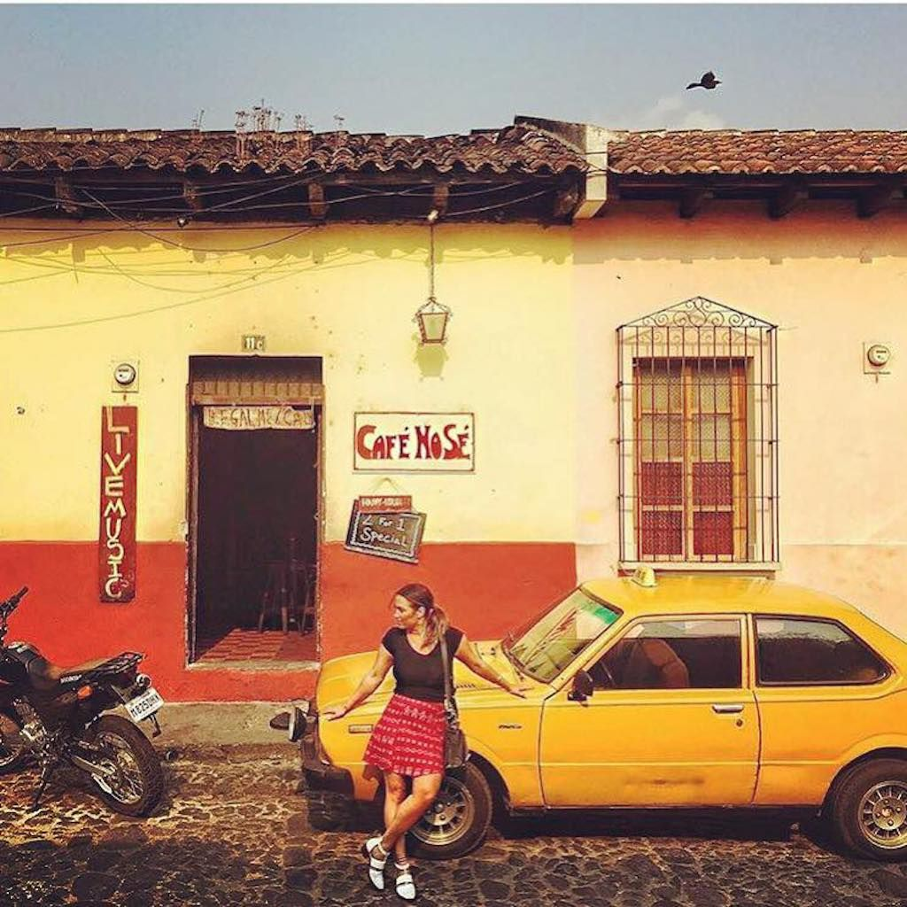 Girl posing with yellow car outside bar in Antigua, Guatemala