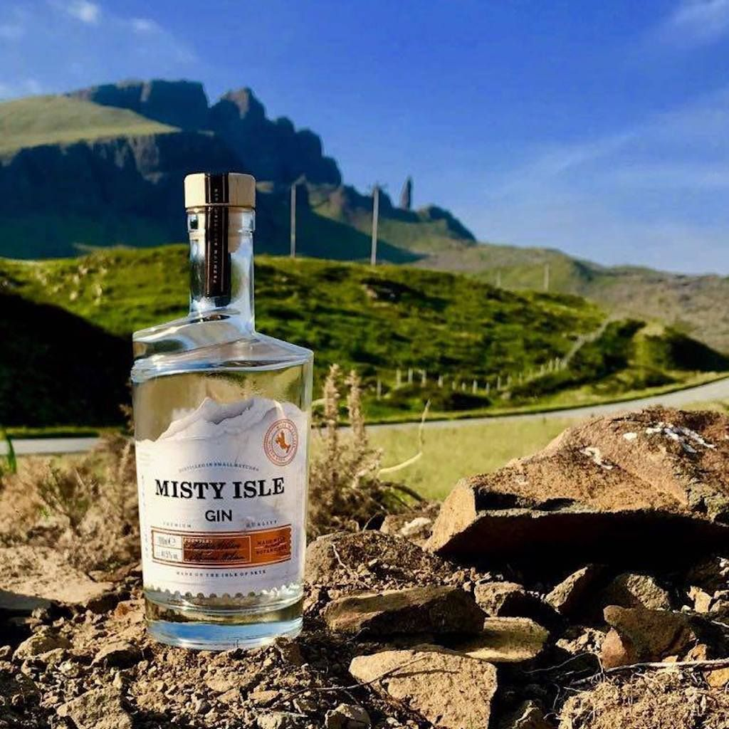 Isle Of Skye Distillers Misty Isle Gin bottle in front of a Scottish landscape