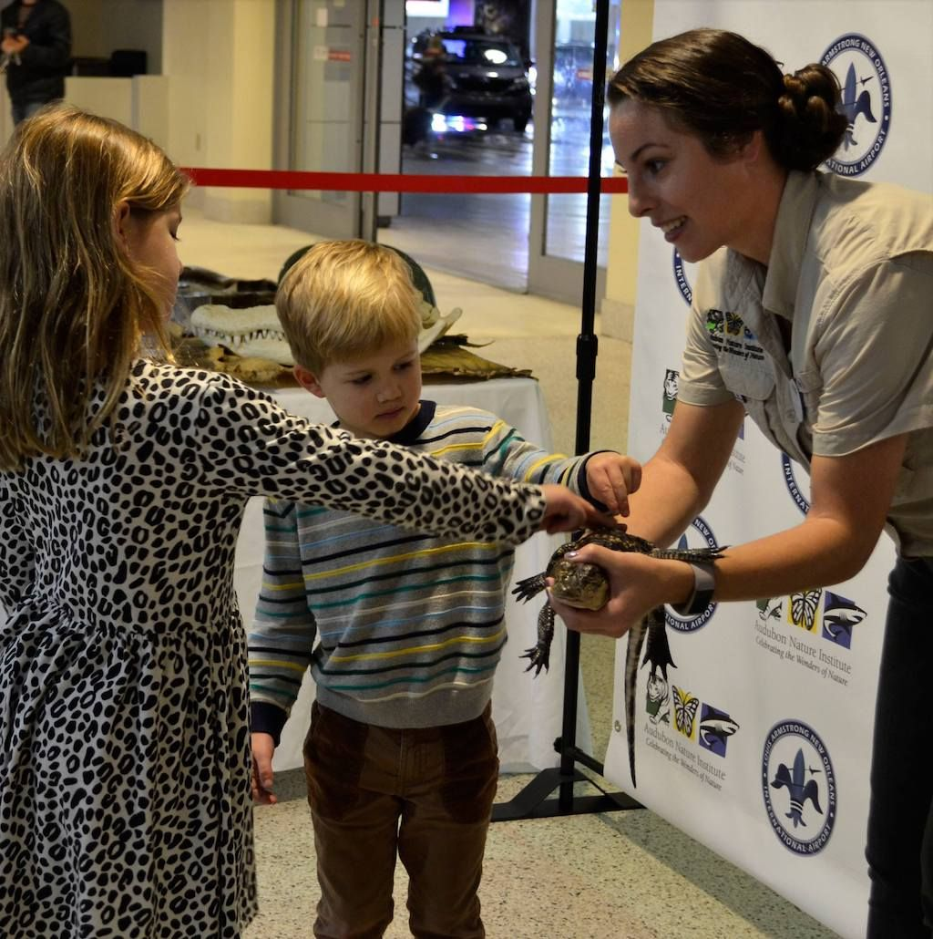 Kids petting a baby alligator at New Orleans airport