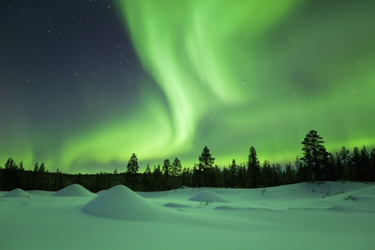 Northern lights over a snowy landscape