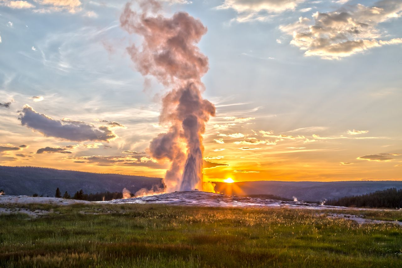 Old Faithful Geyser Eruption in Yellowstone National Park at Sunset