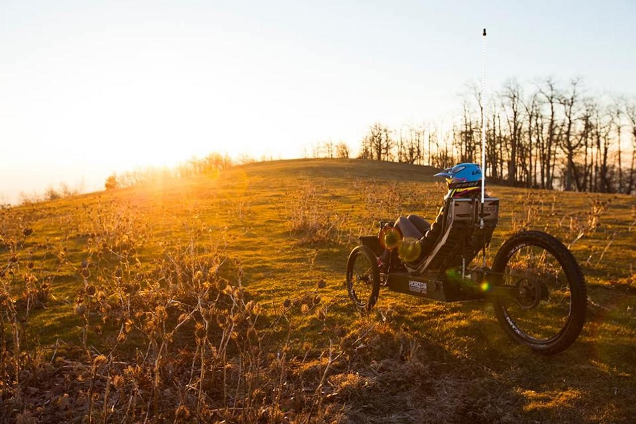 Person in a field on an Outrider bike at sunset