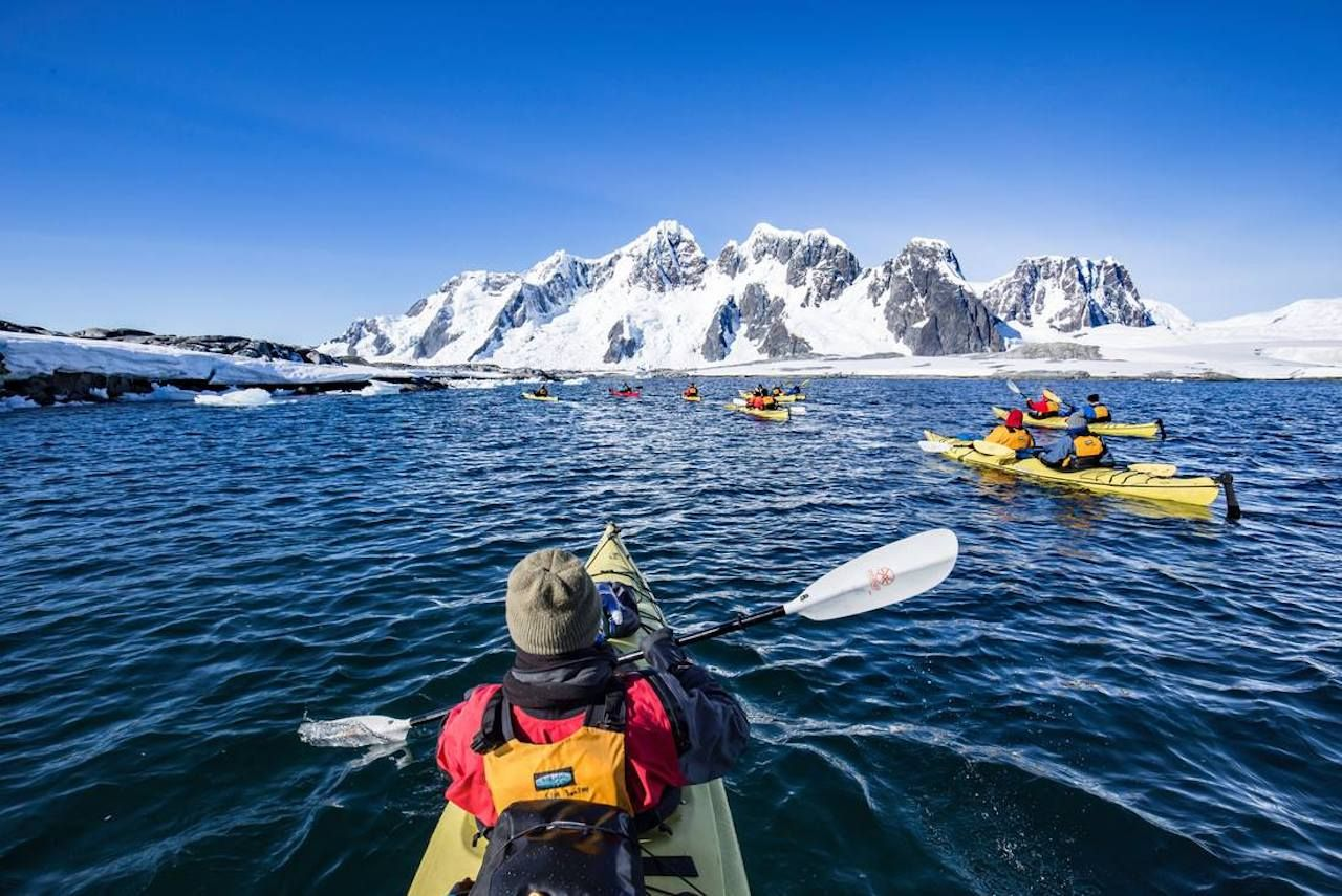 People paddling in waters of Pleneau Island, Antarctica