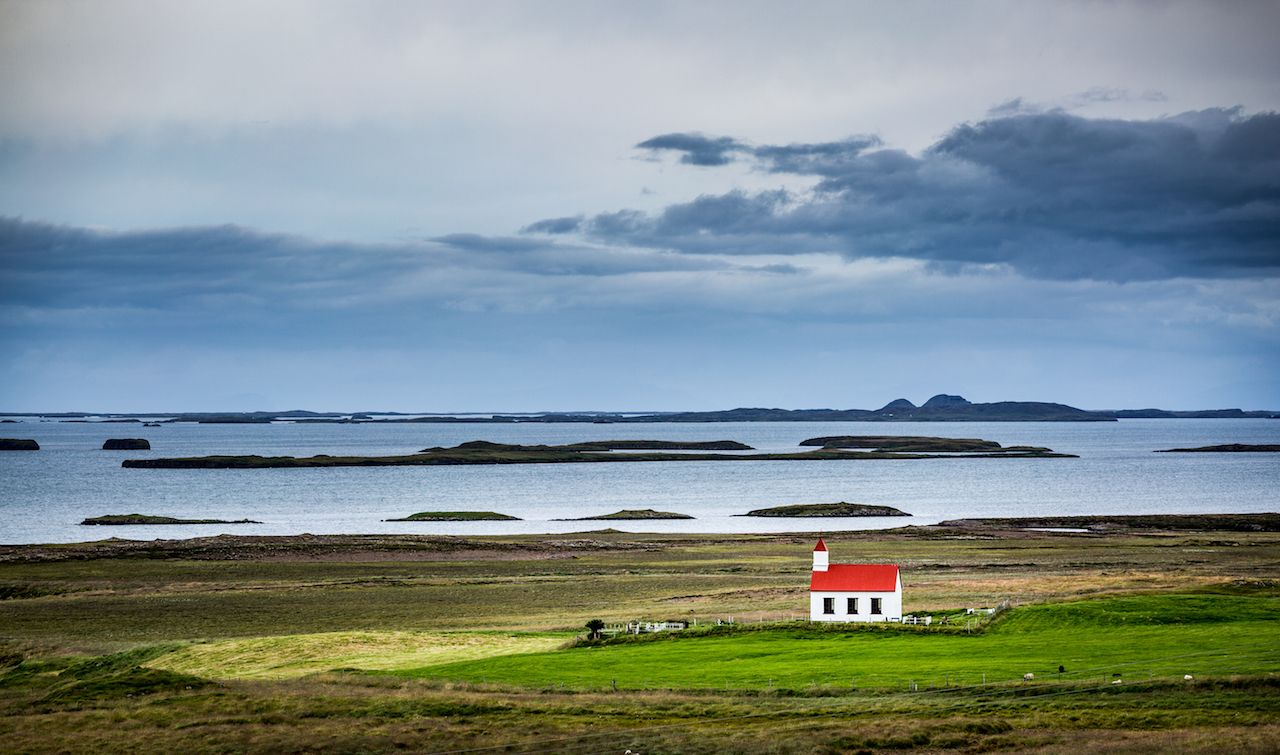Single white, red-roofed church against green grass and water in the westfjords, Iceland