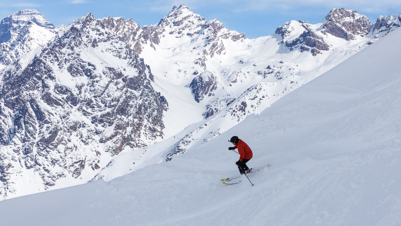 Skier in orange jacket making turns in snow powder