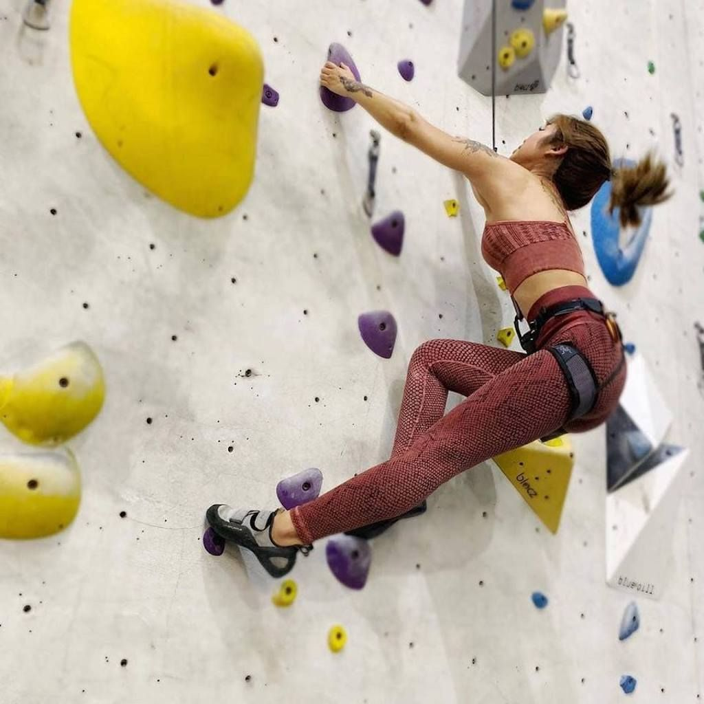 Rock climber ascending a rock wall in a gym
