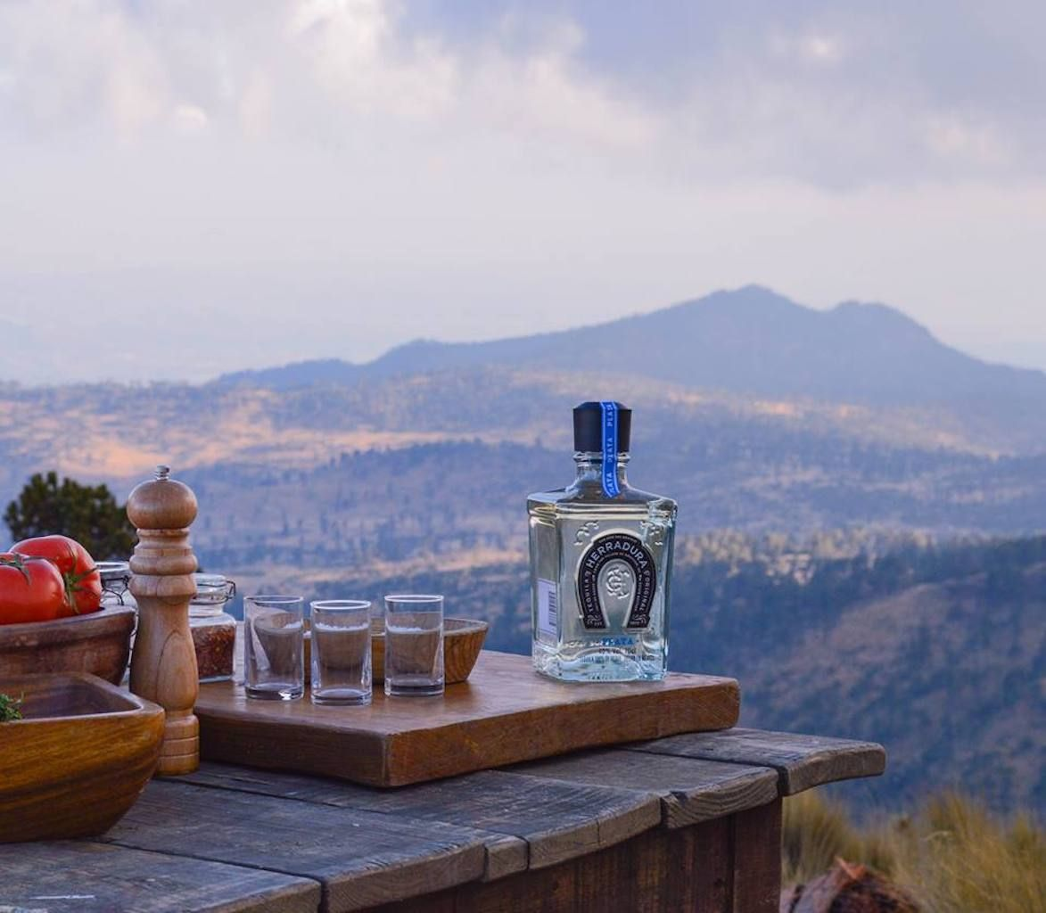 Tequila Herradura bottle and glasses in front of a Mexican landscape