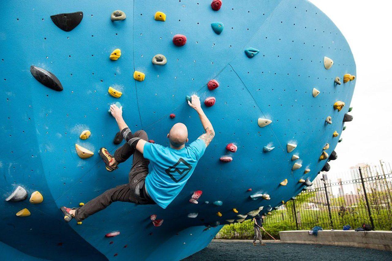 Rock climber on a blue rock-climbing structure