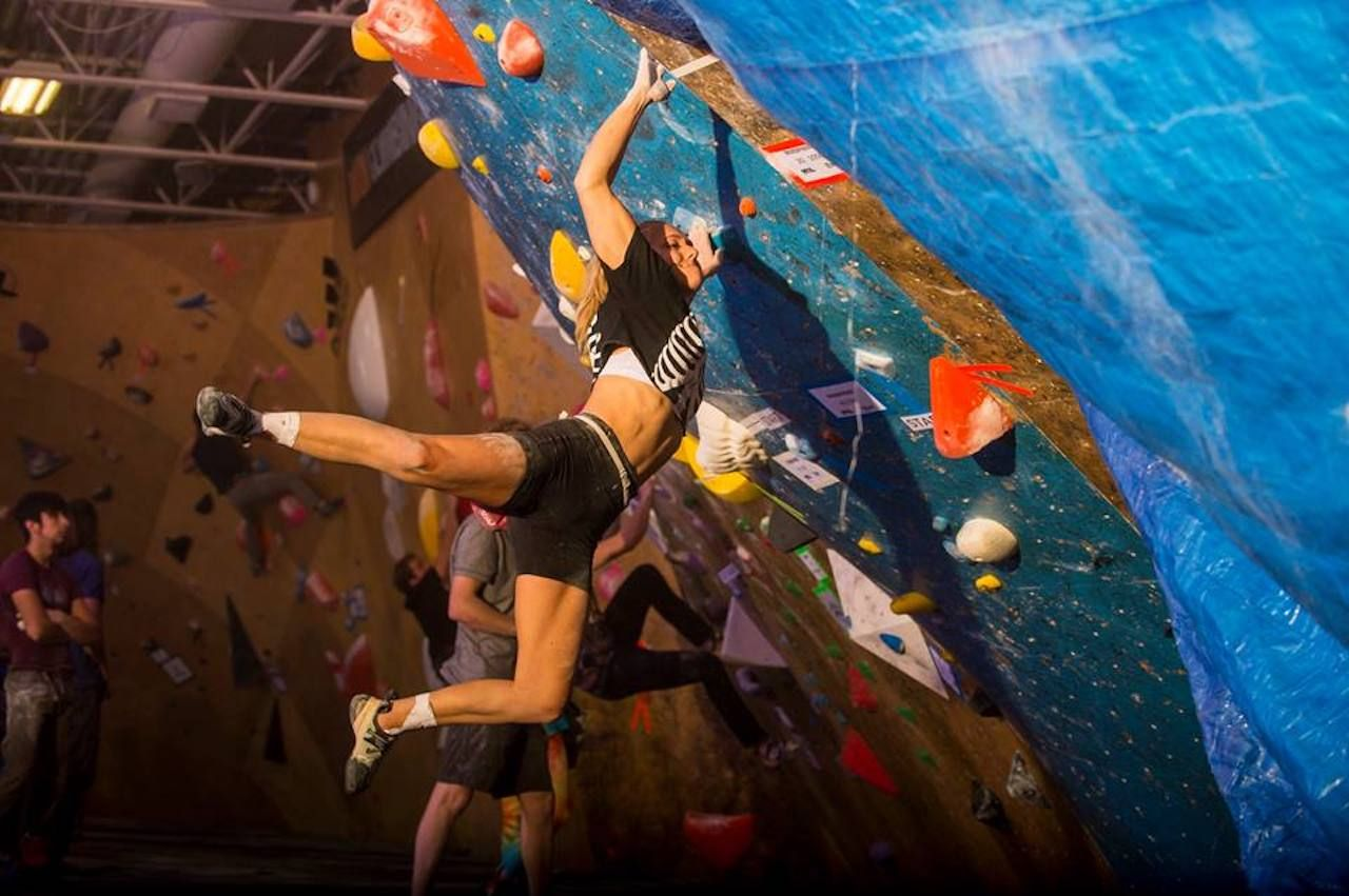 Rock climbing hanging off a rock wall in a climbing gym