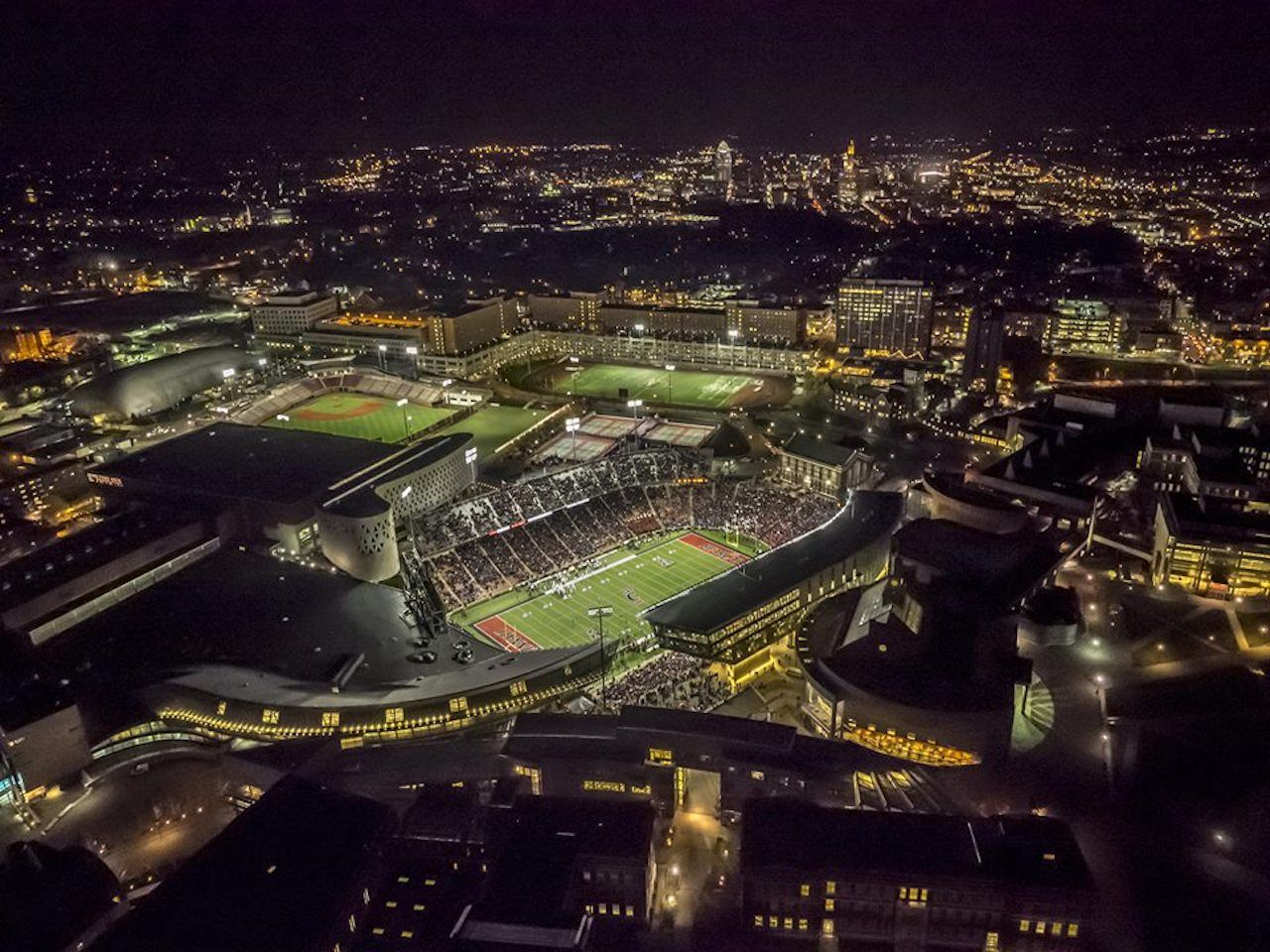 University of Cincinnati football field and cityscape at night