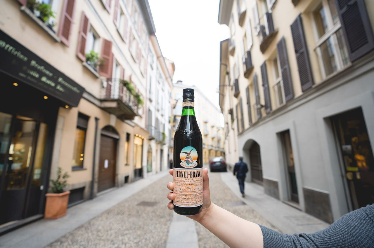 Hand holding bottle of Fernet-Branca in the street
