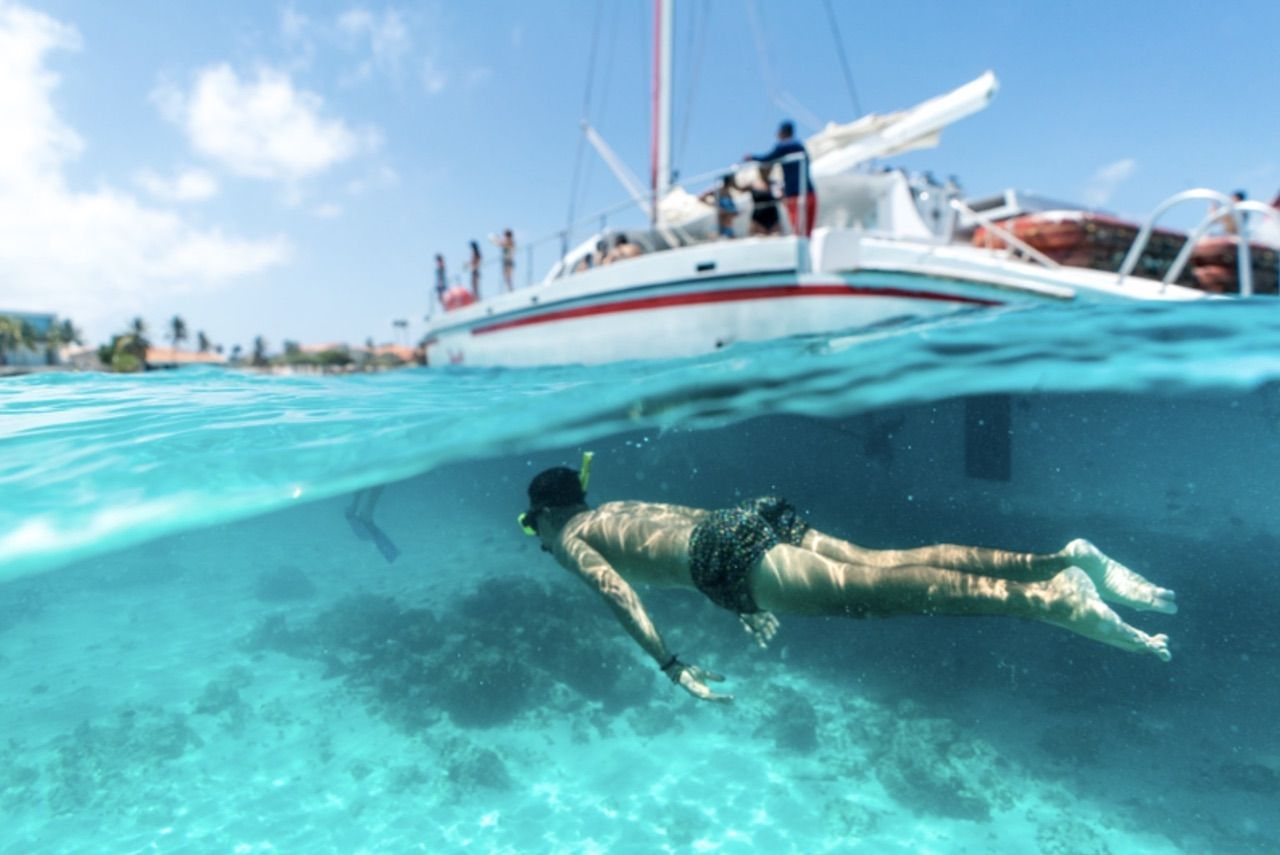 Snorkeler by a boat in the crystal clear water in Aruba