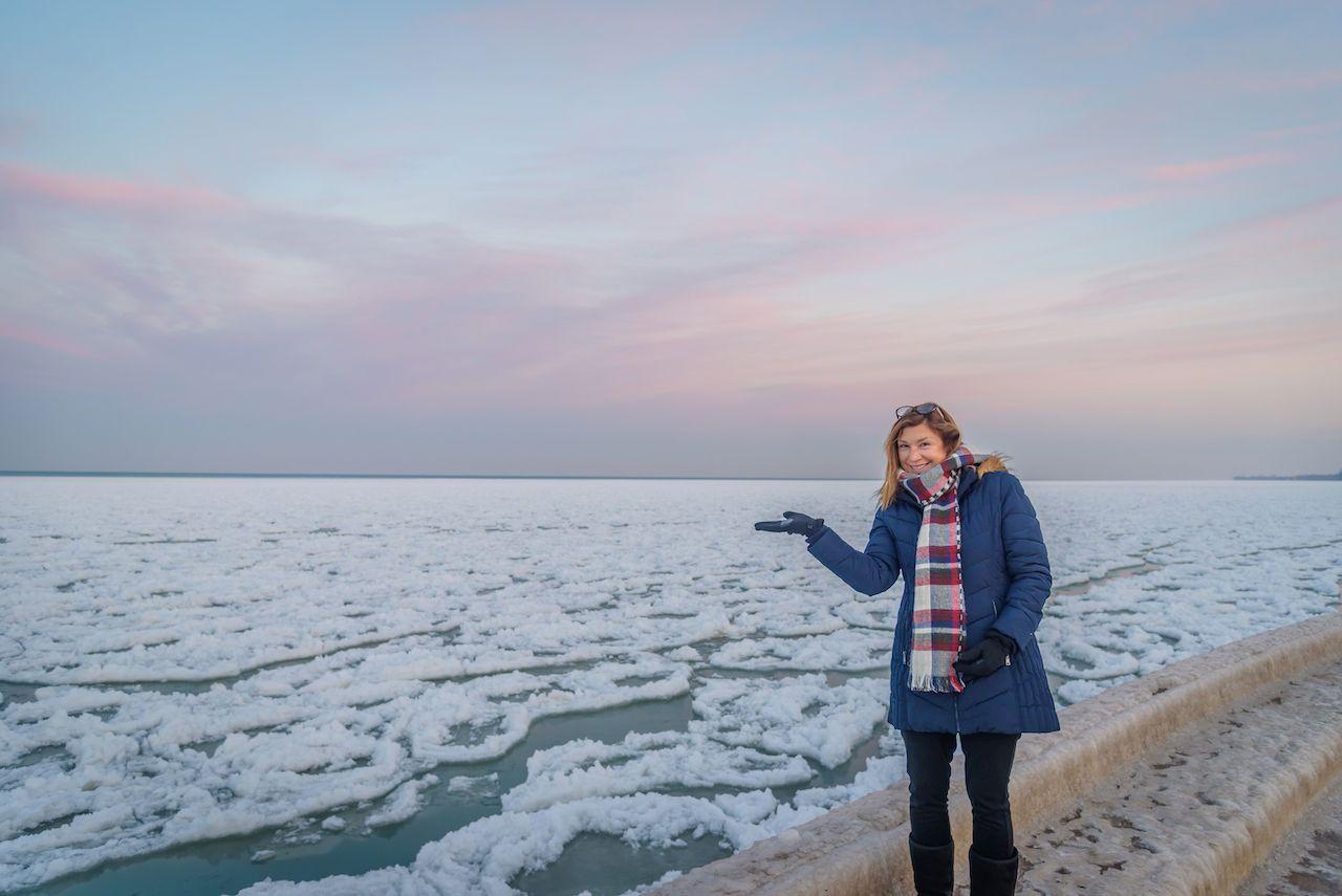 smiling woman walking along lake michigan in winter looking at ice floes