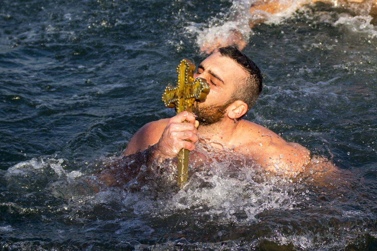 A man kisses a wooden cross during an Epiphany ceremony in Turkey