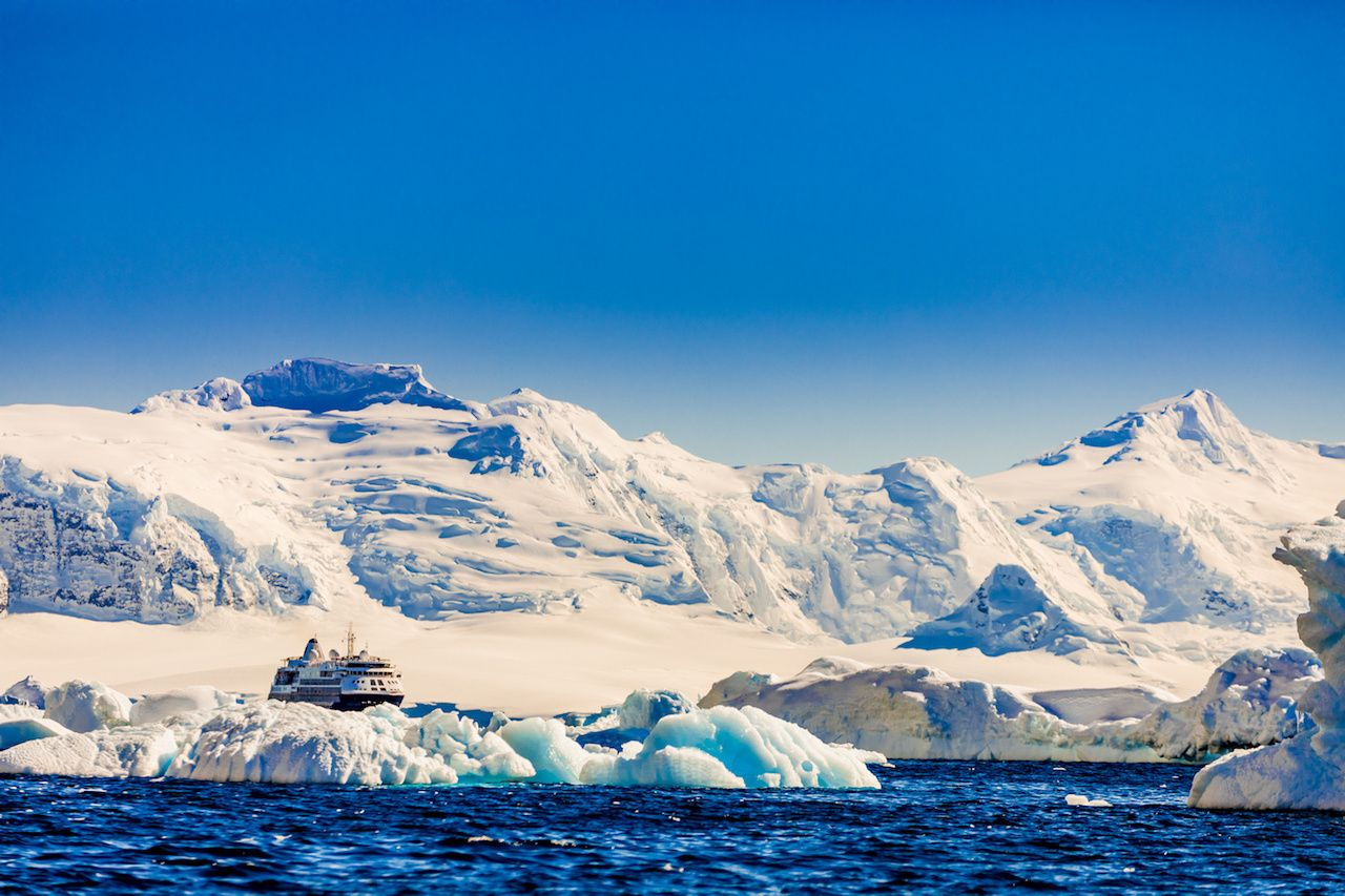 Antarctic cruise ship by glacier