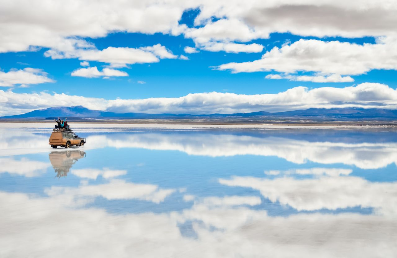 Car driving across Salar de Uyuni salt flats in Bolivia with clouds reflected