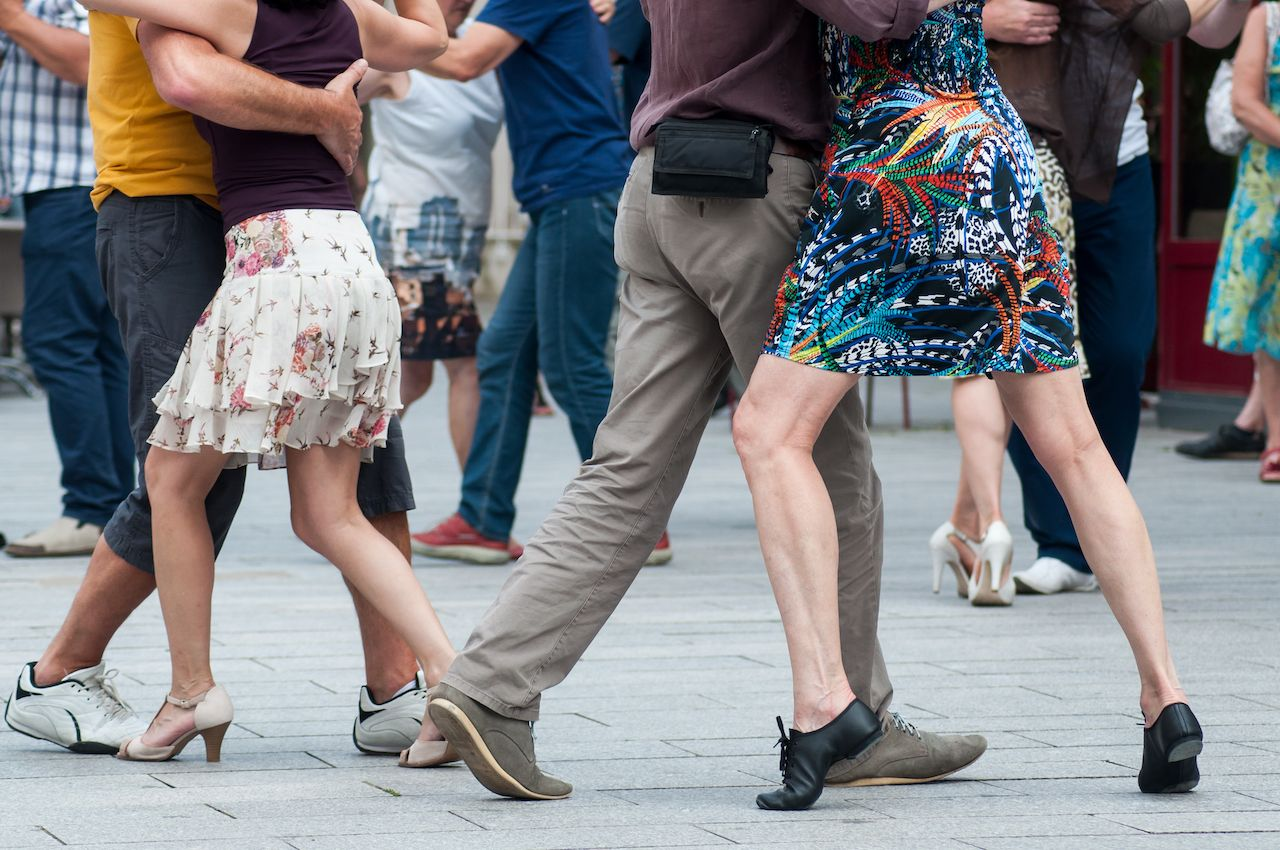 Closeup of legs of tango dancers in the street