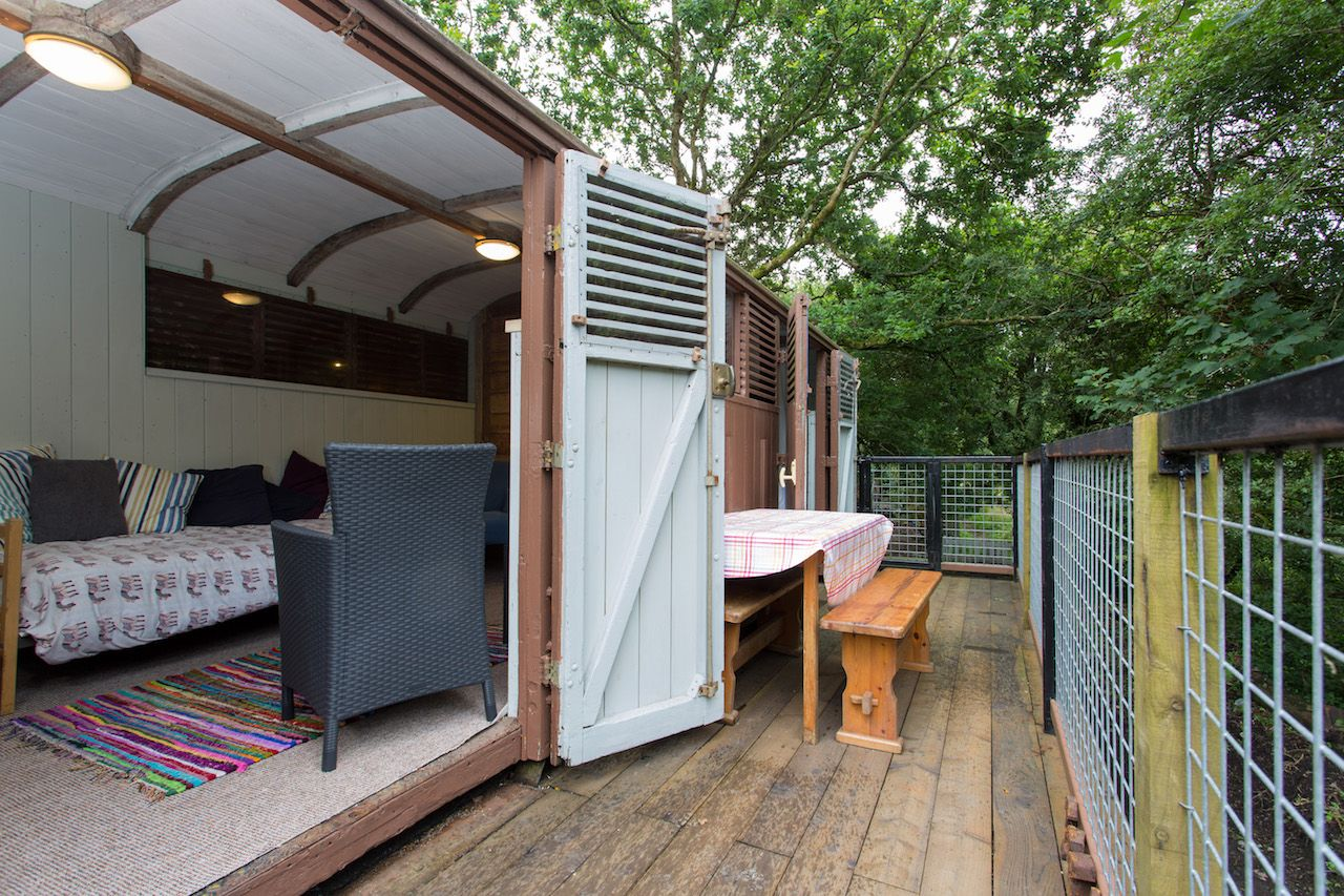 Converted train car turned Airbnb front porch under trees