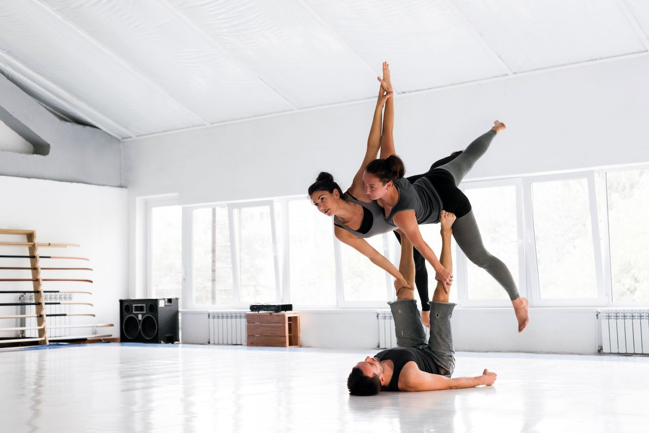 Couple practicing acroyoga in white studio