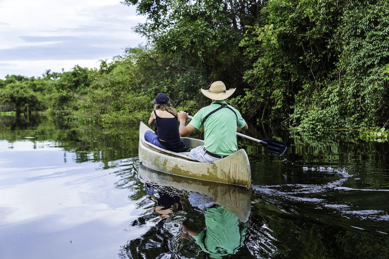 Couple riding canoe in Pantanal River, Brazil