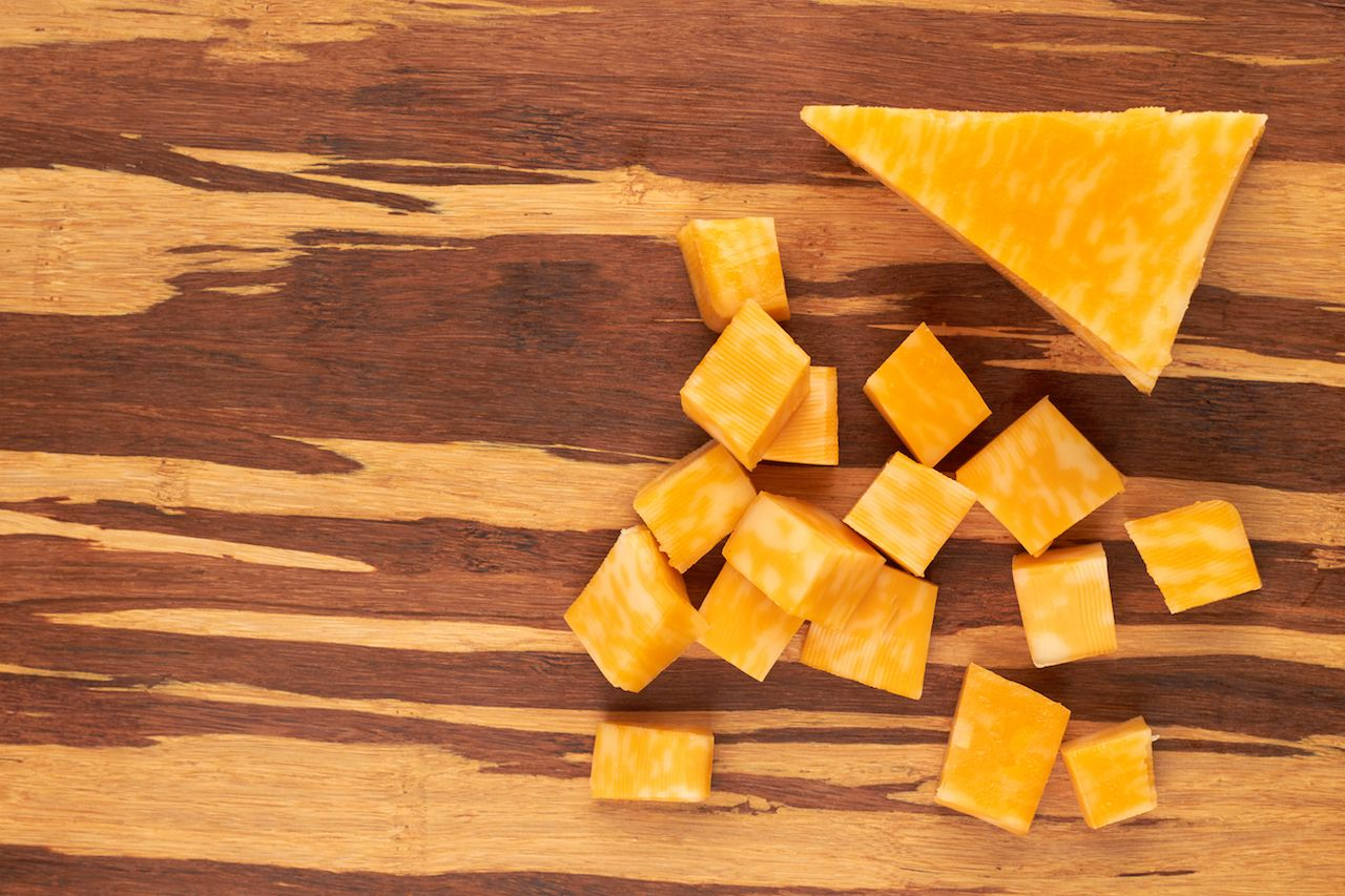Cubes of marble cheese on wooden background