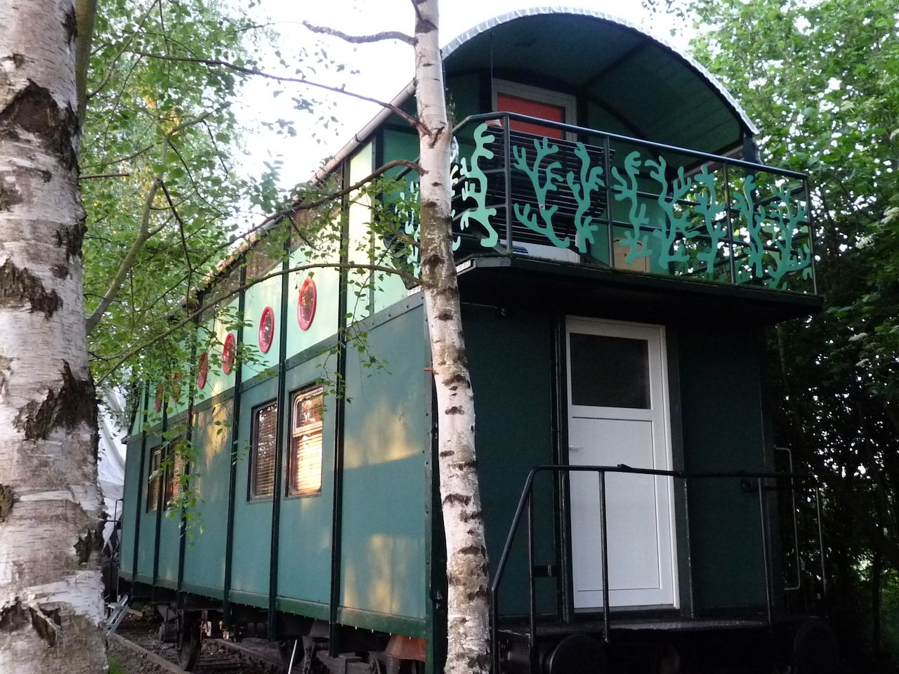 Exterior of a green train cabin converted into an Airbnb
