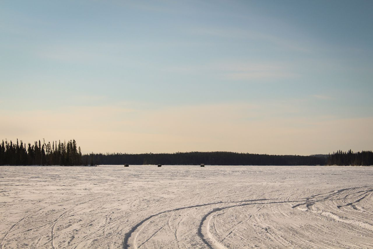 Frozen lake with a lot of anglers enjoying winter fishing