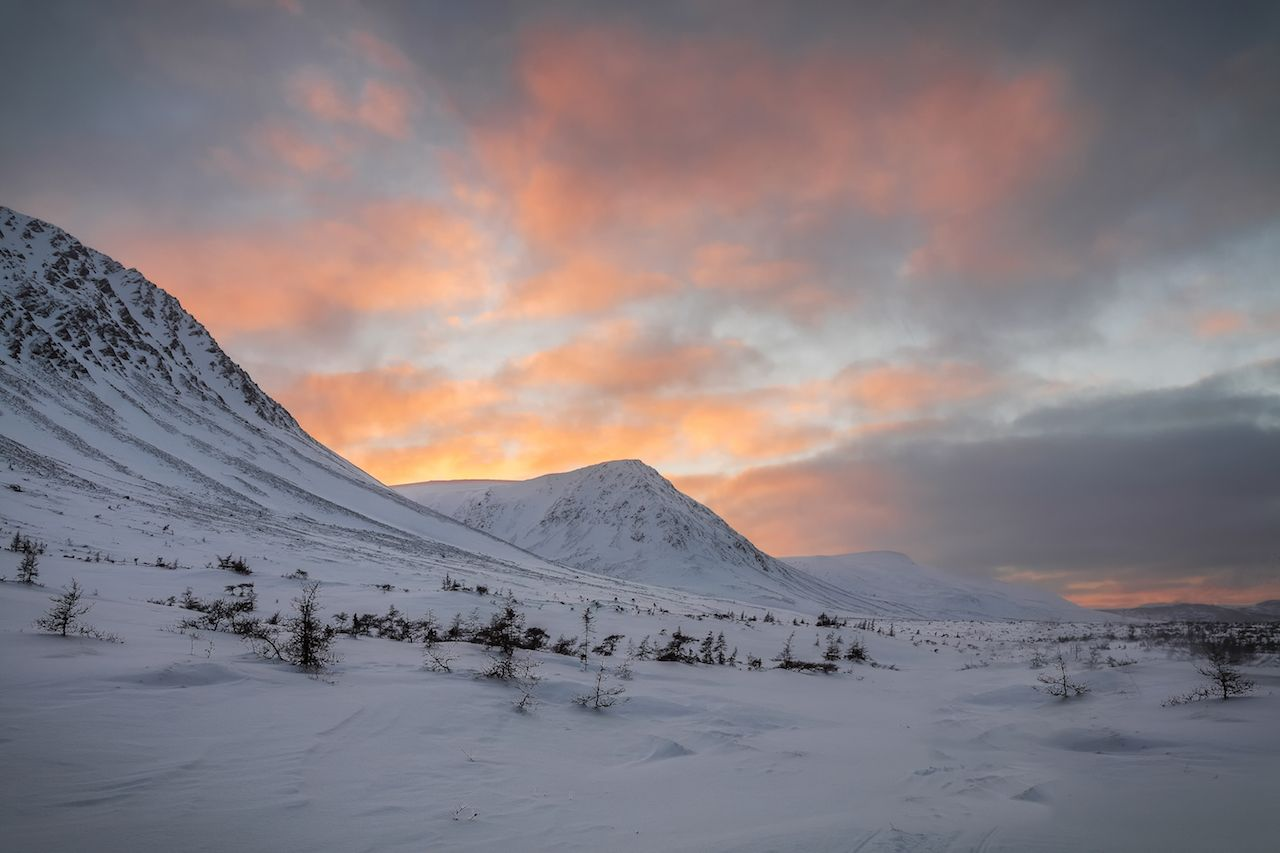 Gros Morne National Park, Newfoundland and Labrador, covered in snow under pink-orange skies