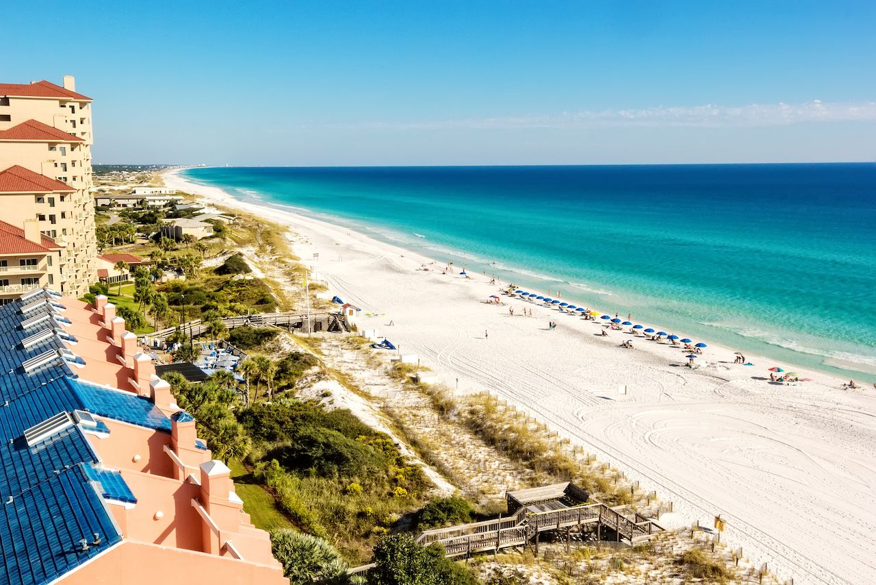 Long stretch of Miramar Beach, in Destin, Florida and the emerald green waters of the Gulf of Mexico