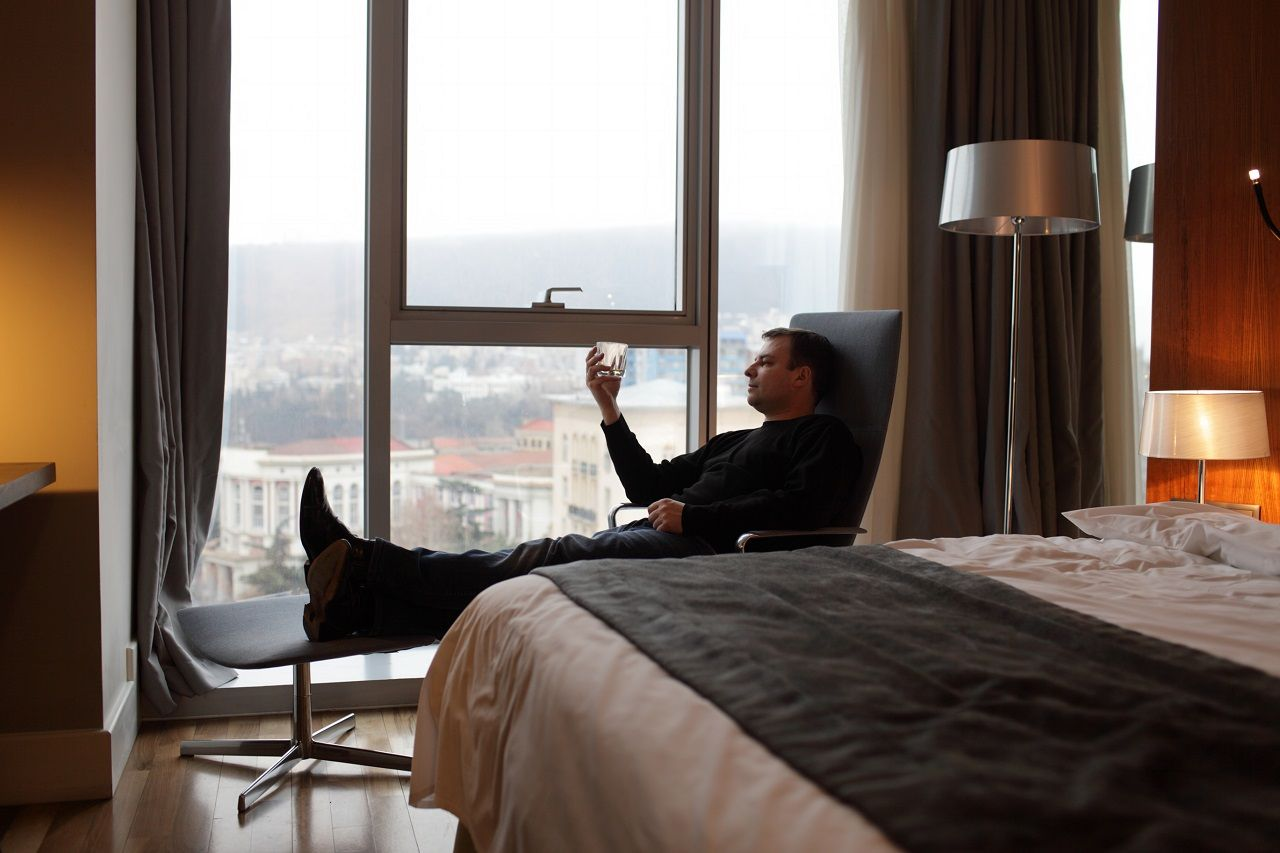 Man in a hotel room with a drink in hand
