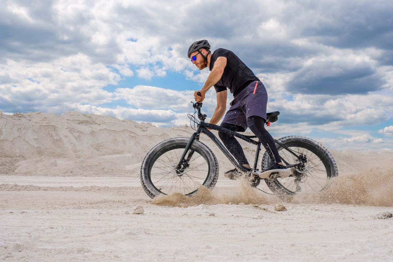 Man riding a fat bike in the sand