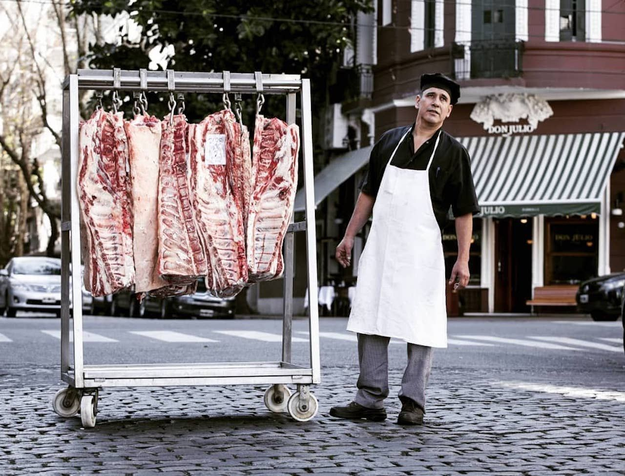 Man standing by rack of meat