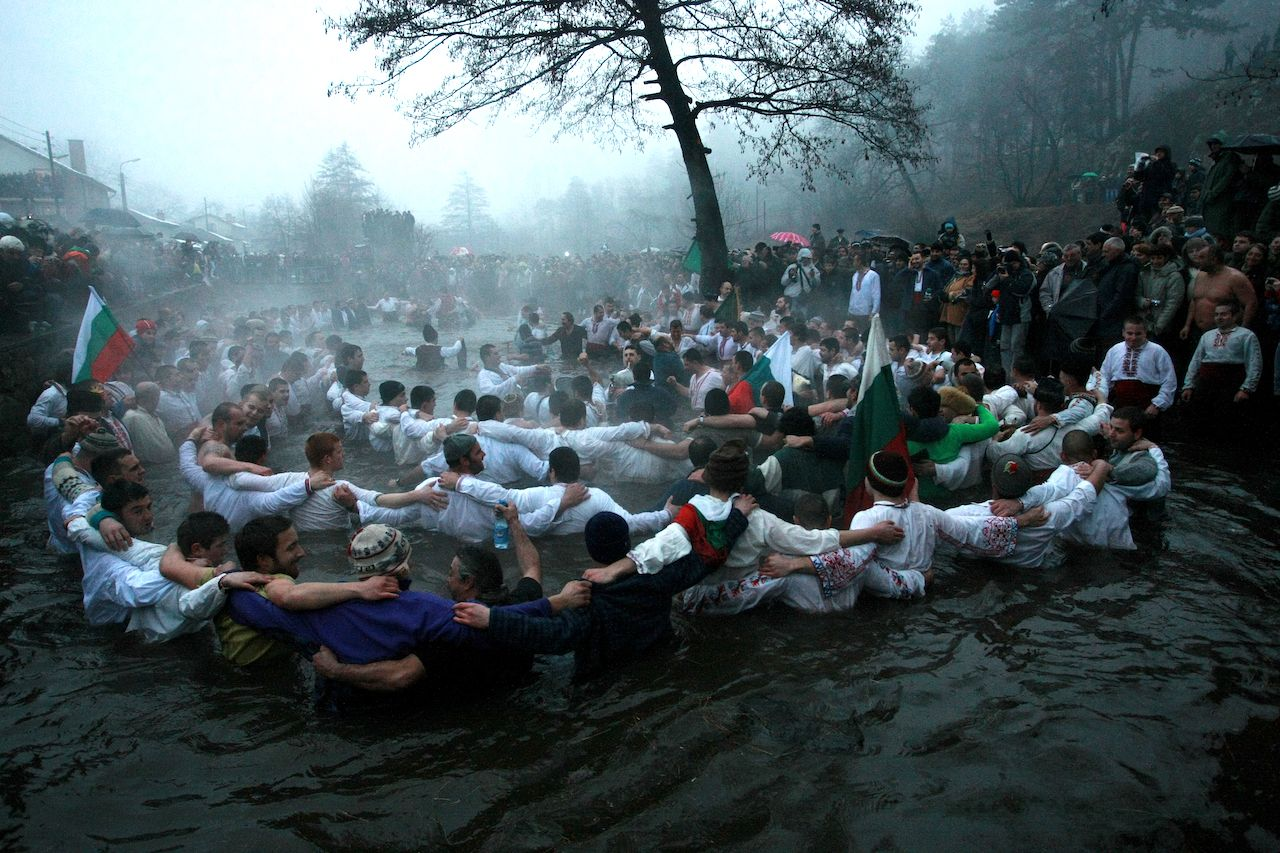 Men perform the national dance Horo in the icy waters of the river in Kalofer, Bulgaria for epiphany celebrations