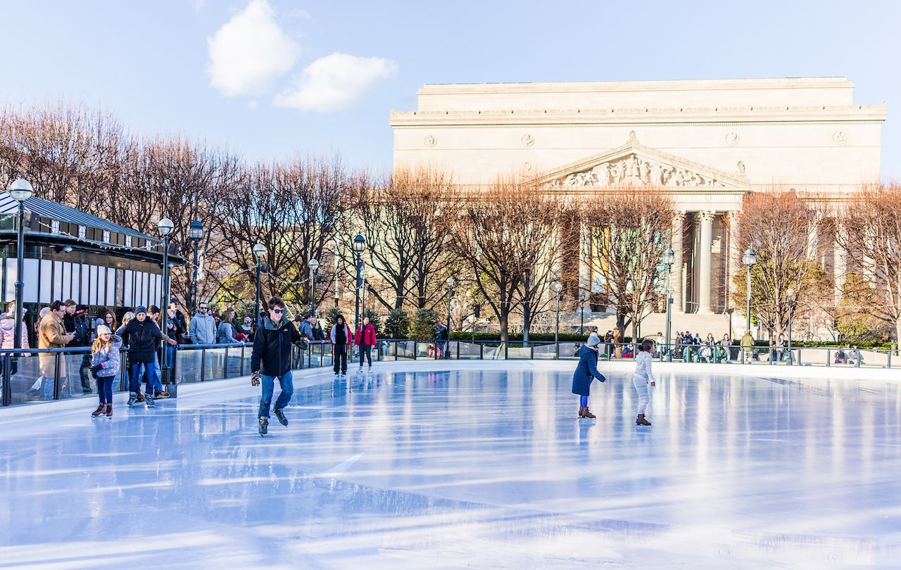 People ice skating in view of a state building