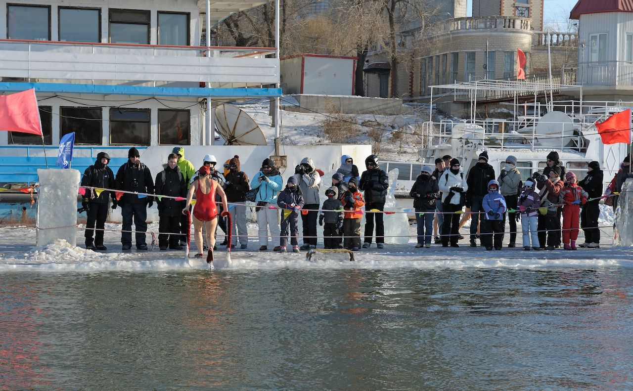 Tourists admiring Harbin's local people taking a dip in hole cut in icy Songhua river during famous, annual Harbin Ice and Snow World Festival in China