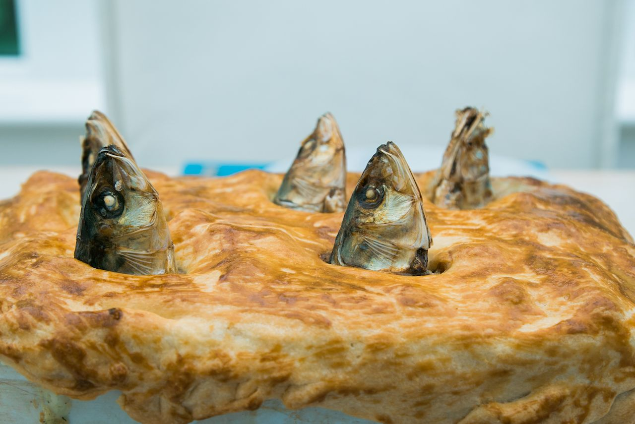 Traditional Stargazy pie wtih fish heads sticking out of the crust from Mousehole, Cornwall, England