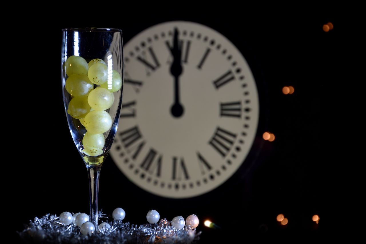 Twelve grapes in a Champagne glass with a clock in the background