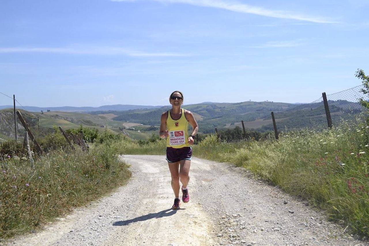 Woman running a marathon through the Italian countryside