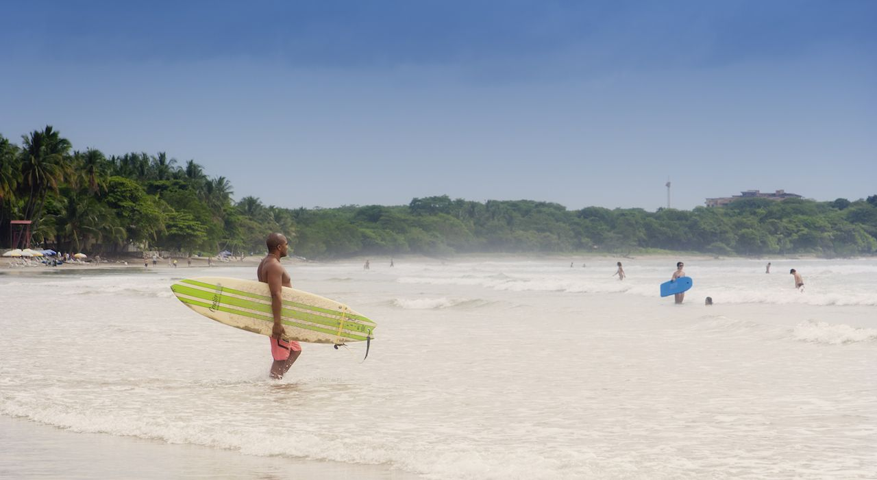 Young man walking with his surfboard into sea in Tamarindo, Costa Rica