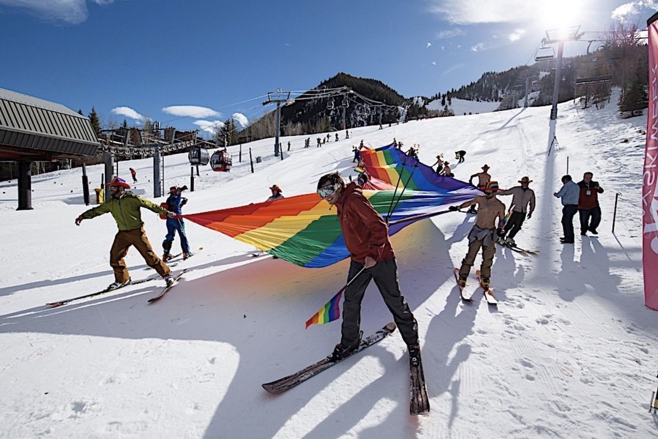 aspen gay ski week skiers holdng rainbow flag