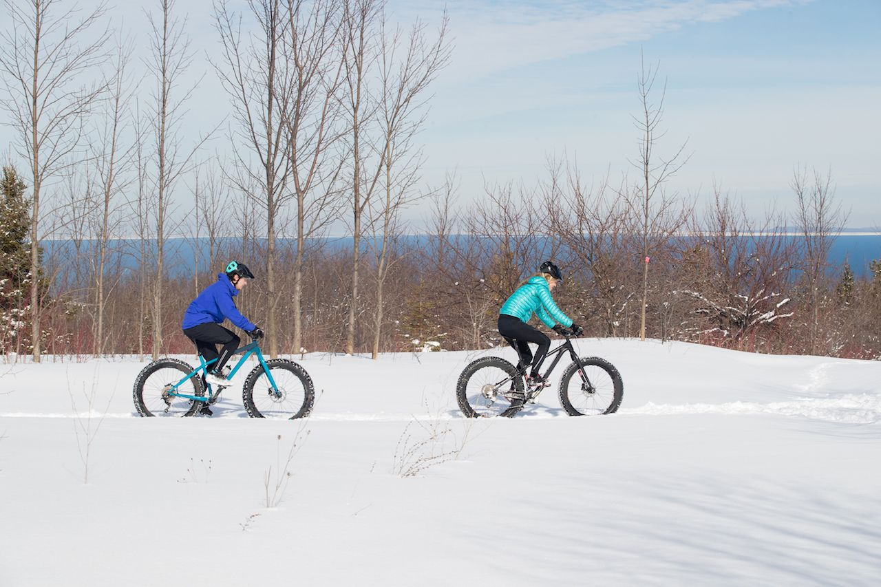 couple rides their fat bikes on a trail in the snow