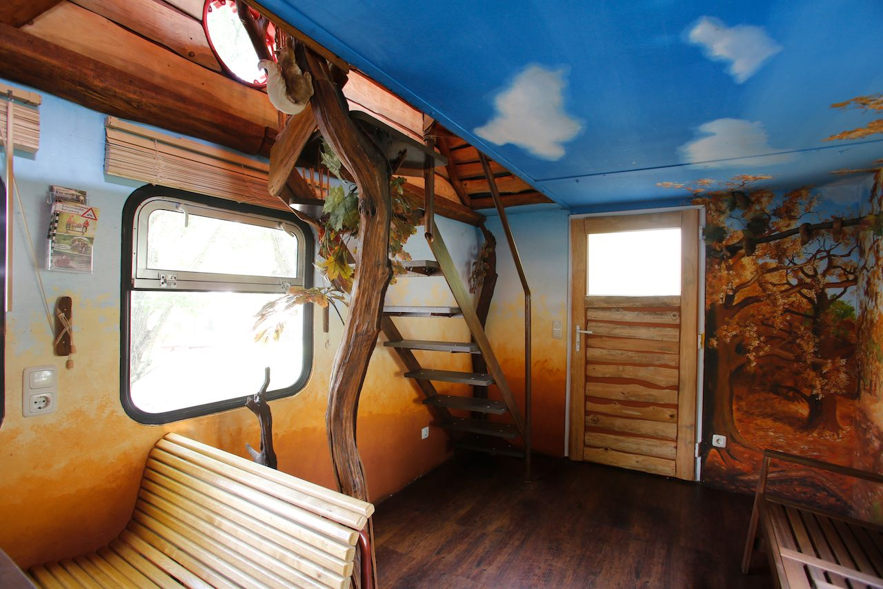 forest scene painted inside a train car converted into an Airbnb