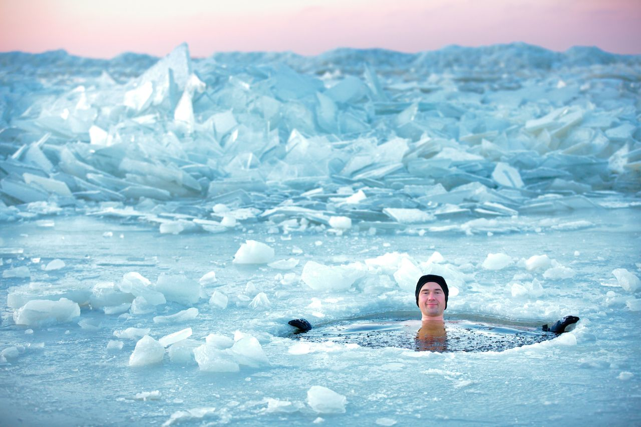 man swimming in an ice hole