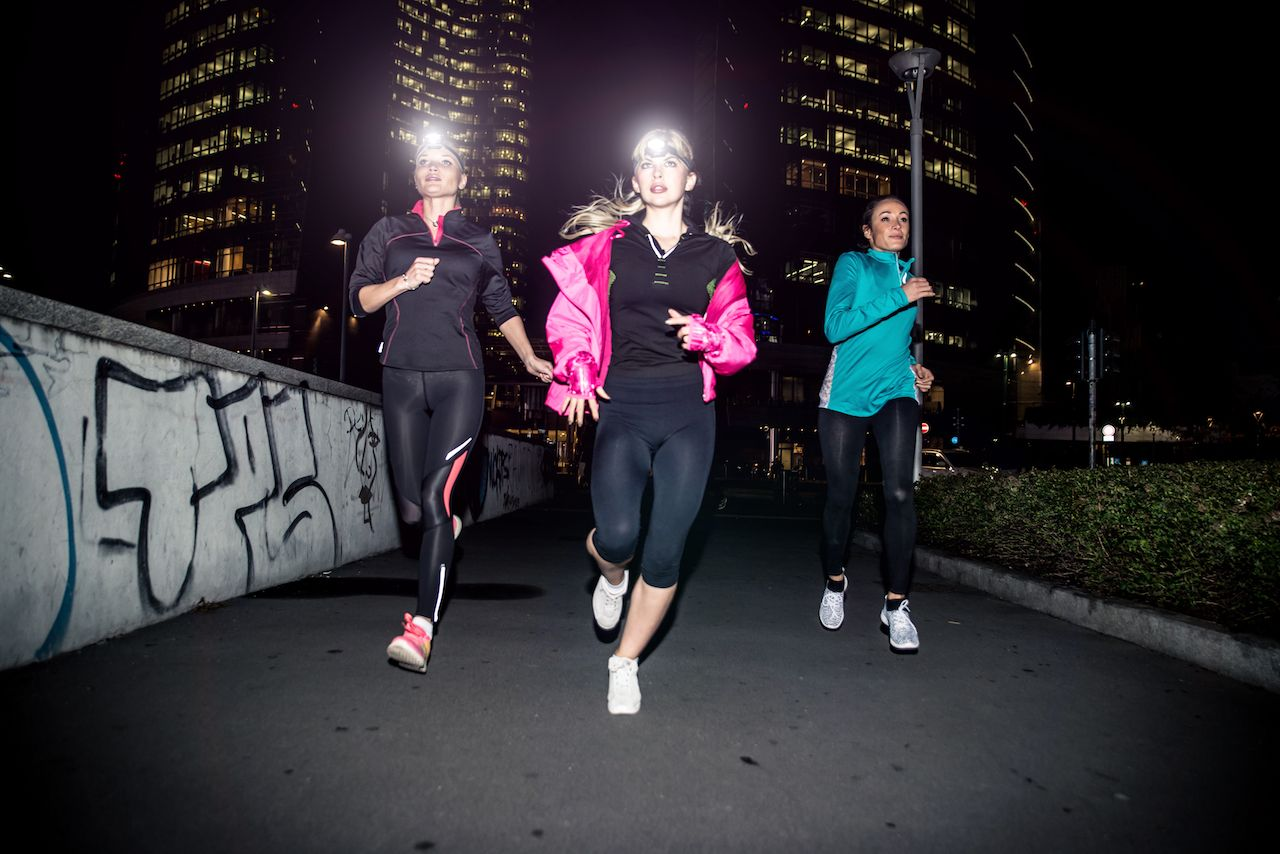 three women night running downtown