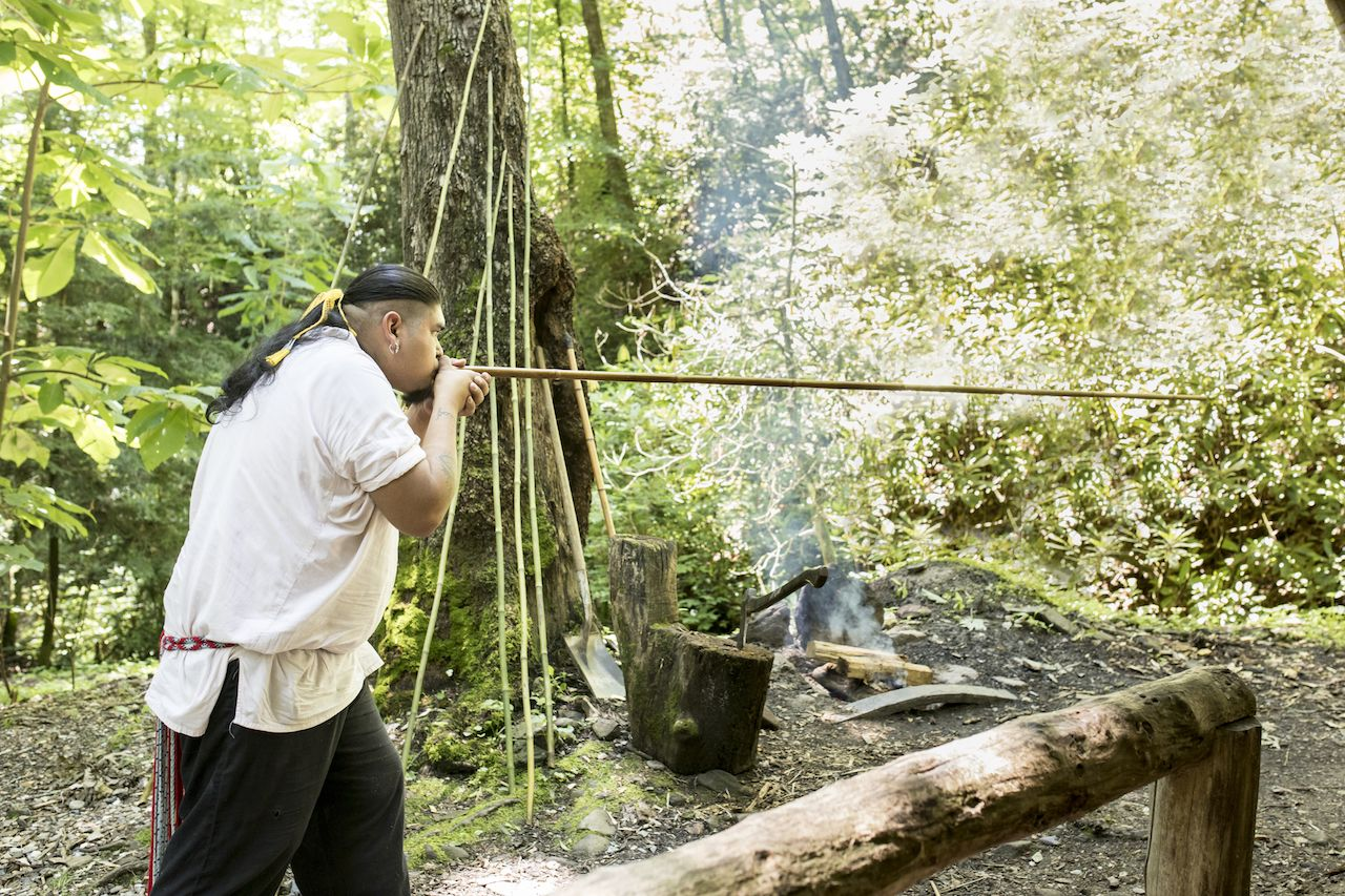 A Cherokee Indian uses a traditional blowgun