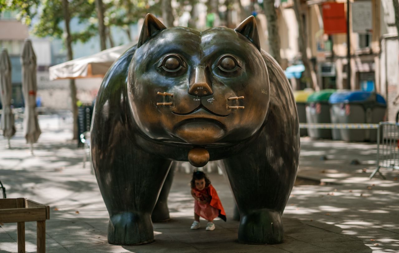 A child plays underneath a bronze cat sculpture in downtown Barcelona